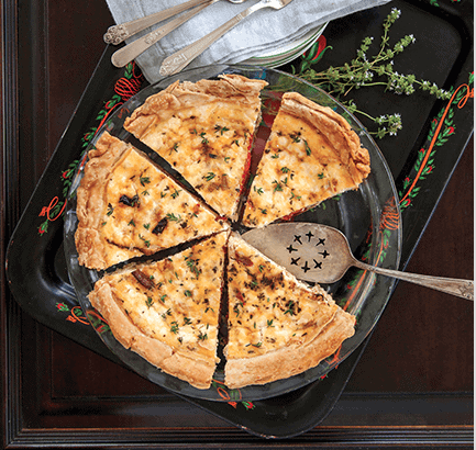vegetable quiche in a glass pie plate with fresh herbs and a serving utensil served as breakfast at a b&b asheville nc