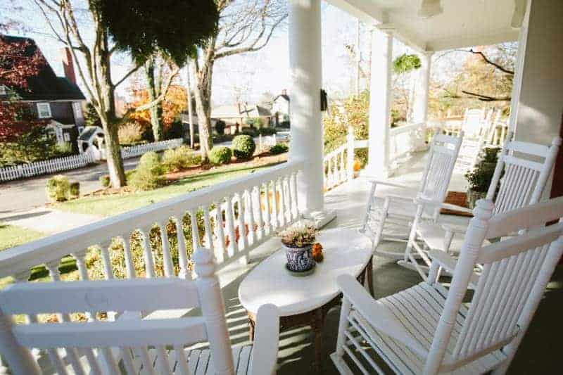white rocking chairs on the front porch at an asheville bed and breakfast
