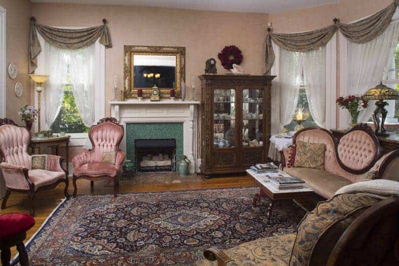 sitting room with pink chairs and a pink couch with purple rug and pink wallpaper and a green fireplace at a bed and breakfast near asheville