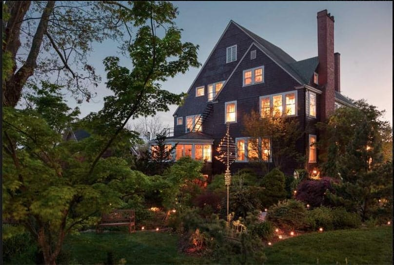 front of the whitegate inn a bed and breakfast near asheville, nc at dusk with the inside illuminated