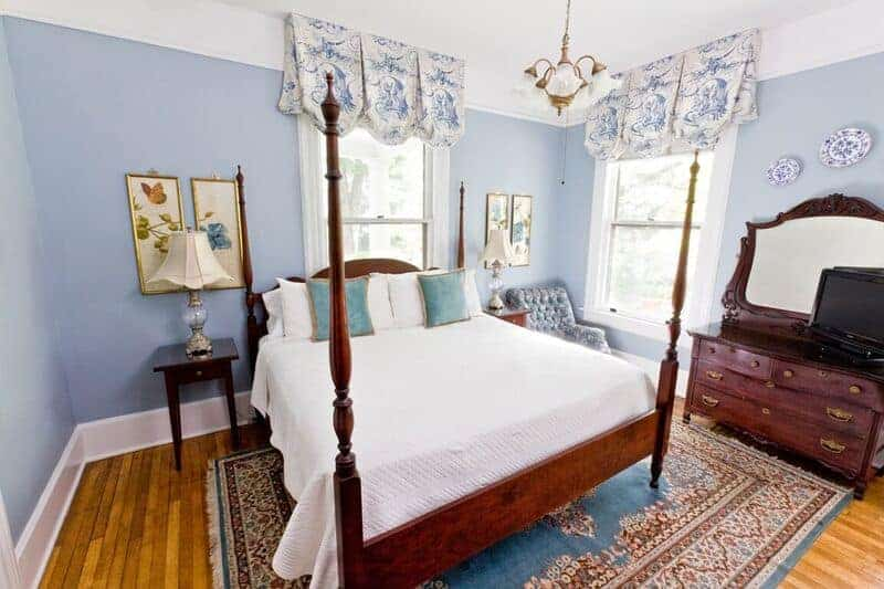blue painted bedroom at an asheville bed and breakfast with wooden 4 post bed and wooden dresser