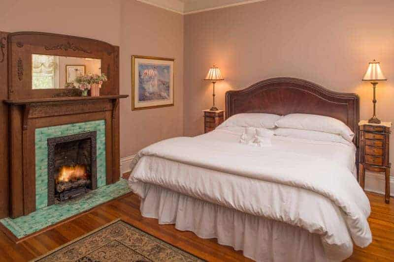 wooden bed with white linens and a wood and green tiled fireplace at an asheville bed and breakfast