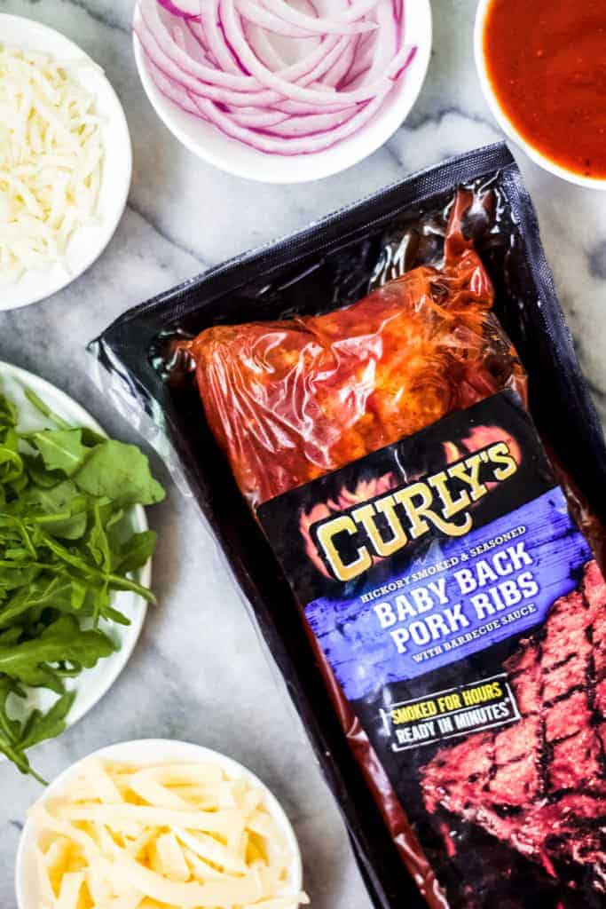 curly's ribs with other ingredients needed like arugula, cheese, red onion and bbq sauce for a grilled bbq pizza on a marble board