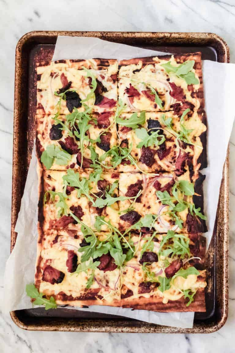 grilled bbq pizza on parchment paper and a baking sheet pan with ribs, red onion, gouda cheese and arugula