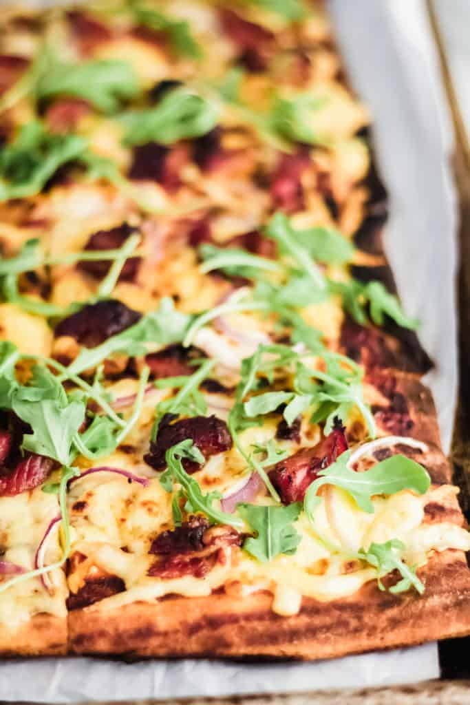 corner of a square grilled pizza with bbq ribs on parchment paper