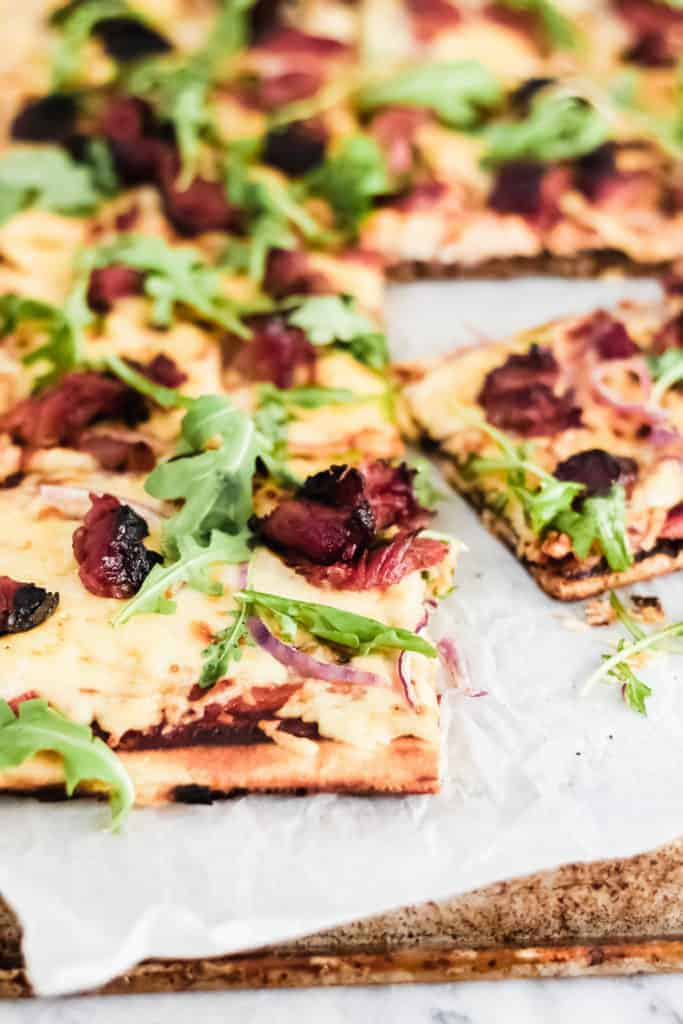 slice of grilled bbq pizza on parchment paper with arugula and bbq ribs