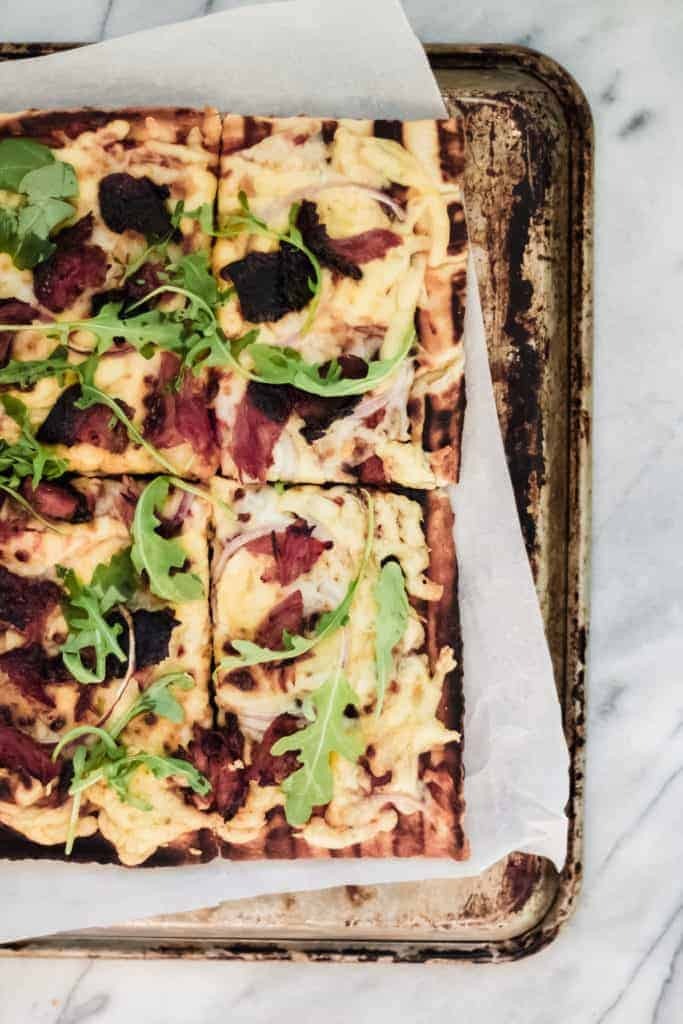 grilled bbq pizza on a sheet pan and marble surface