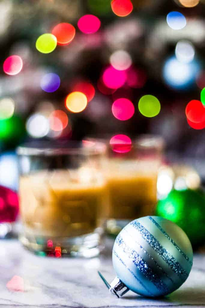 a blue christmas ornament with glitter with eggnog white russian cocktails in the background