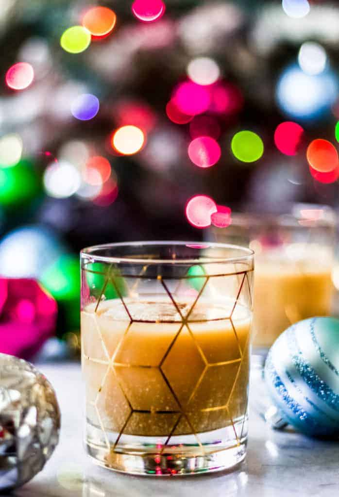 a glass of christmas white russian cocktail made with eggnog in front of a christmas tree