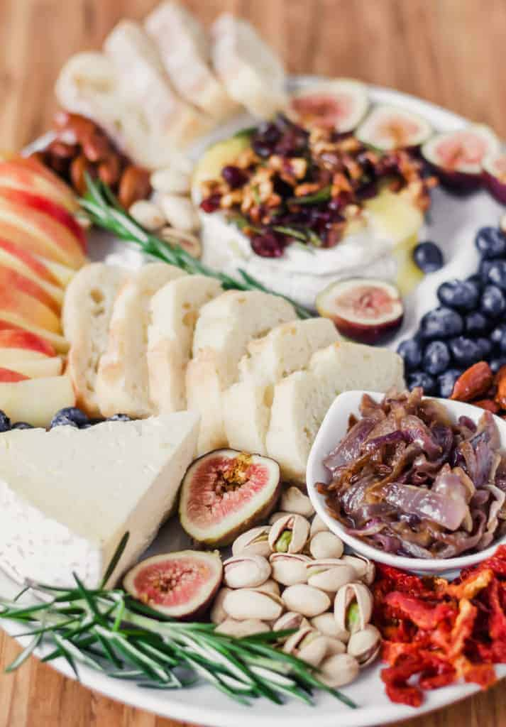 cheese board on a white platter and a wooden surface with fruit and brie