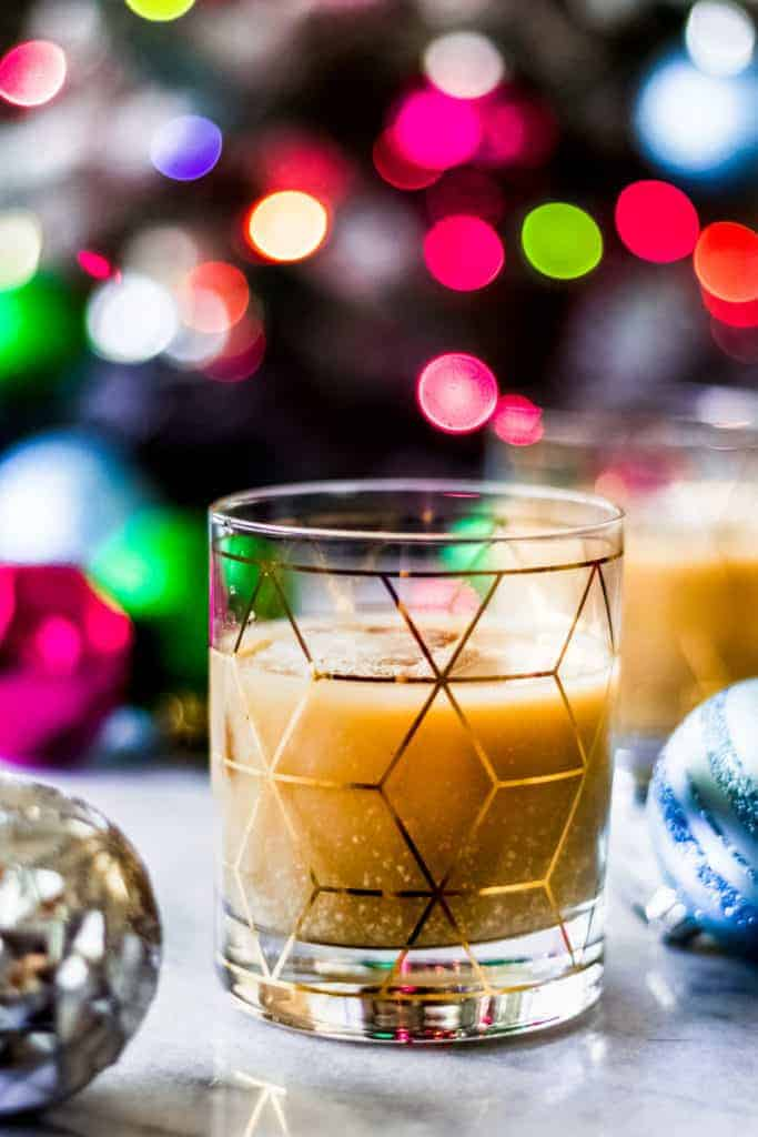 christmas white russian in a rocks cocktail glass with christmas ornaments in front of a christmas tree