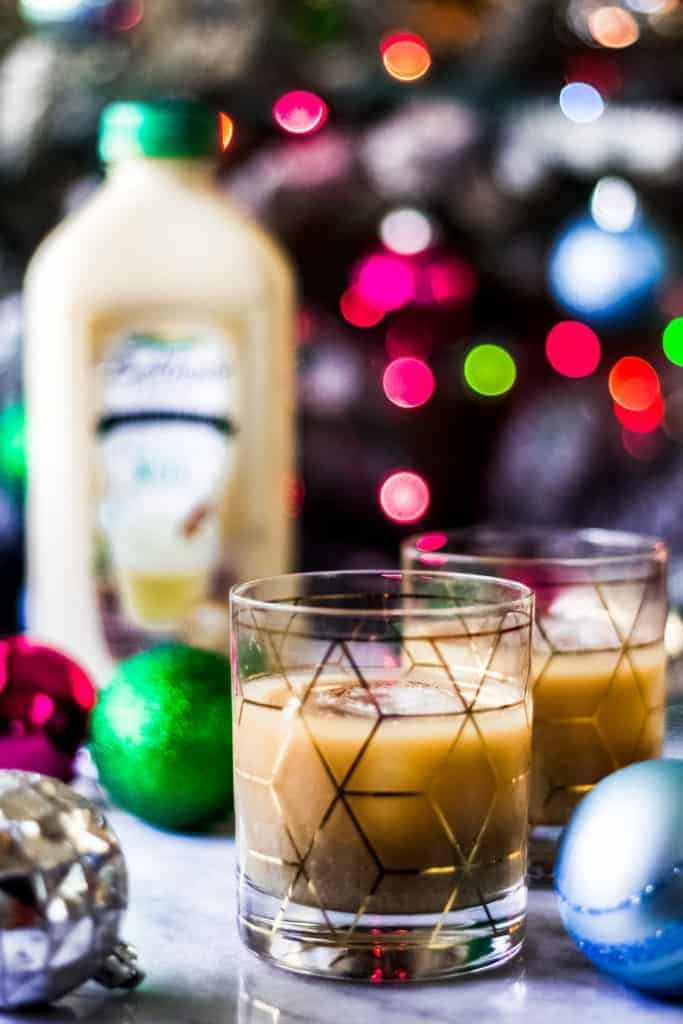 egg nog white russians in front of a christmas tree and a bottle of bolthouse farms holiday nog