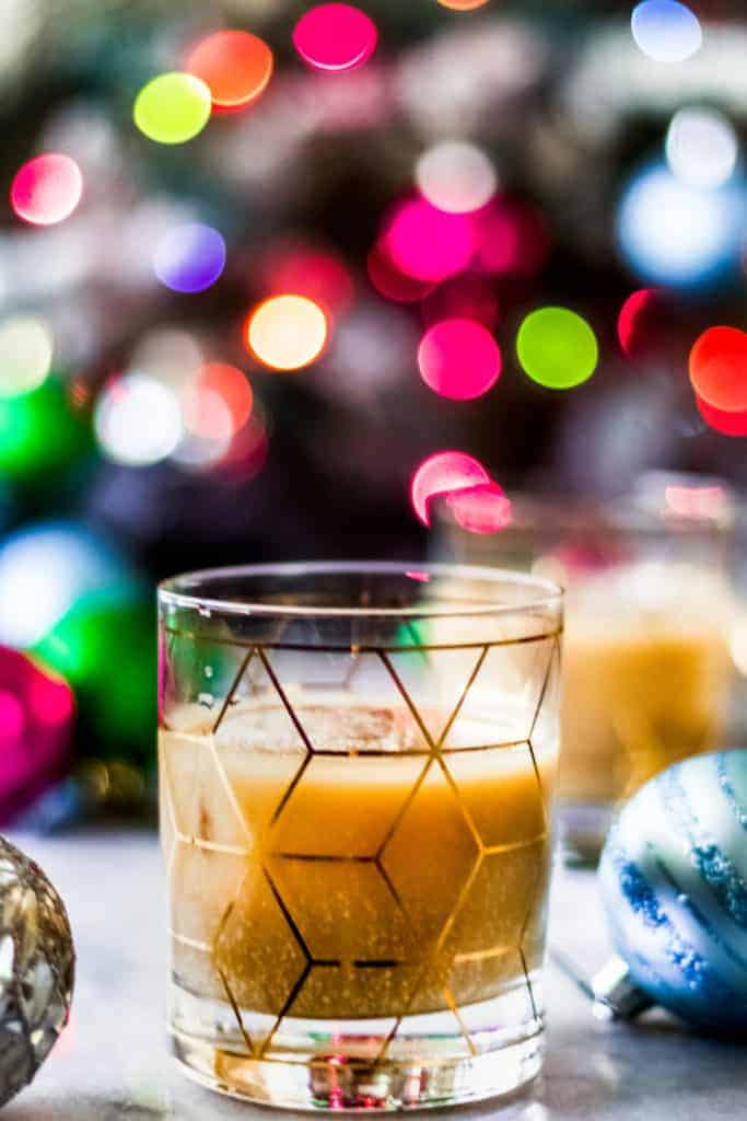 two eggnog white russian cocktails in front of a christmas tree with multi colored lights
