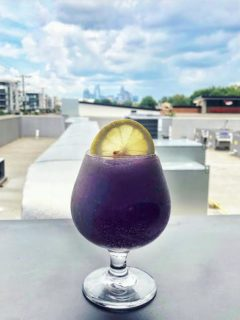 frozen purple hummingbird cocktail with the charlotte skyline in the background at the waterman
