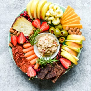 cheese board with cheddar cheese, pimento cheese, apples, strawberries, crackers and other fruit on a teal plate on a grey board
