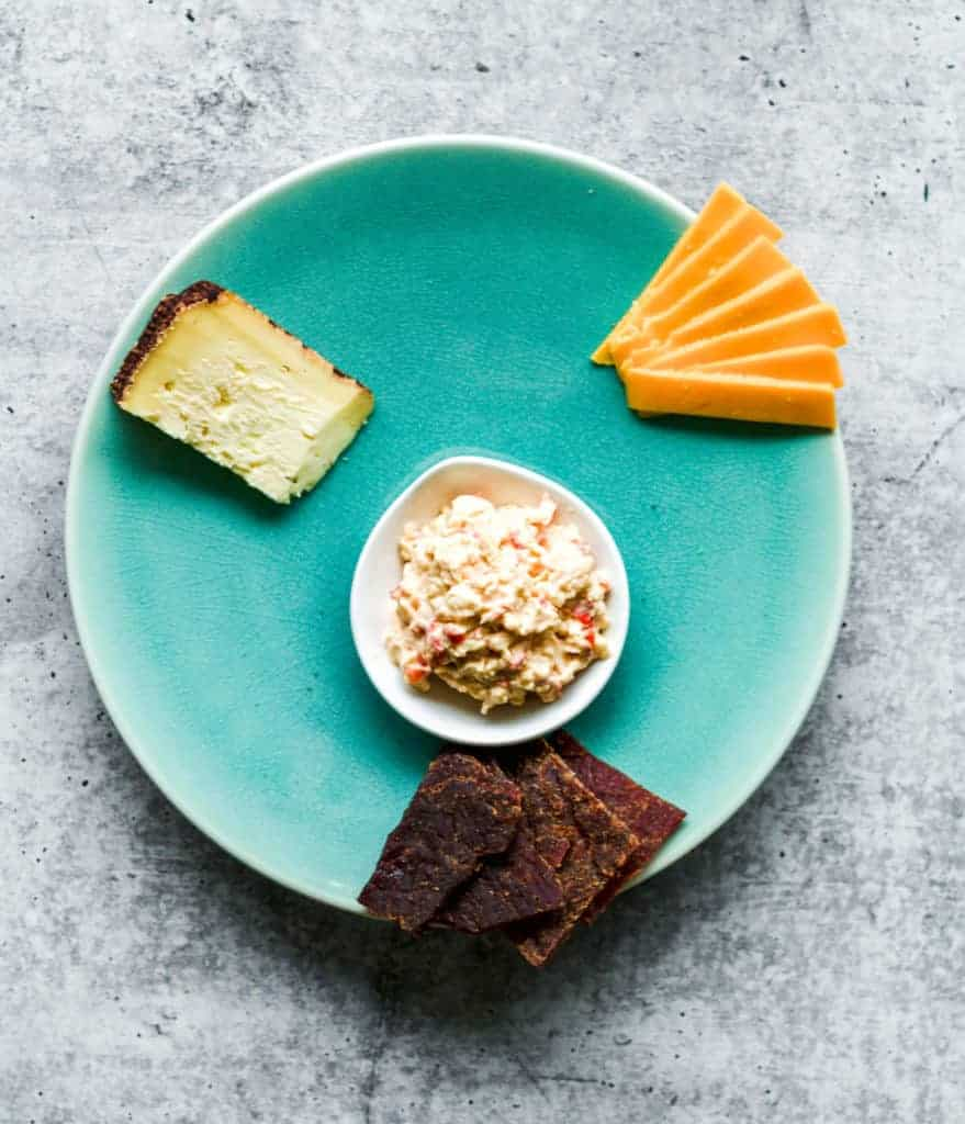 teal plate with cheddar cheese, pimento cheese and beef jerky