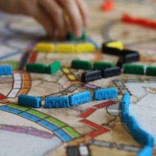 ticket to ride game board with blue and yellow trains and a hand grabbing a game piece dave-henri-FdTmaUlEr4A-unsplash
