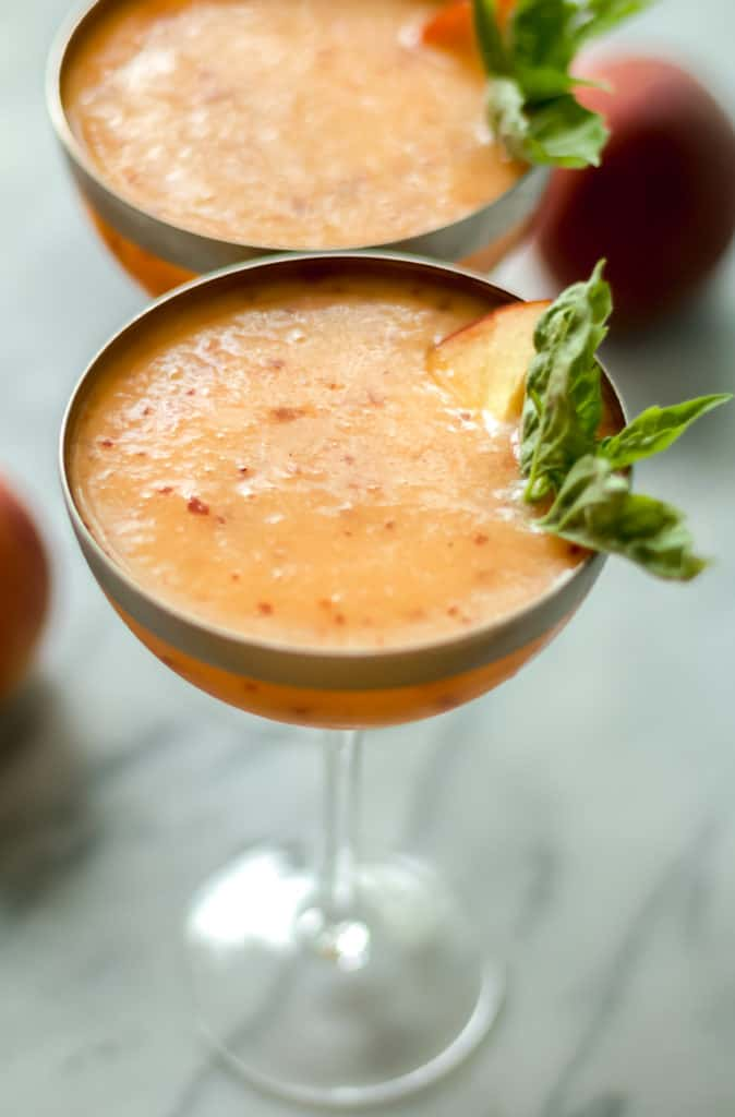 close up angle of peach frose in a cocktail glass garnished with basil