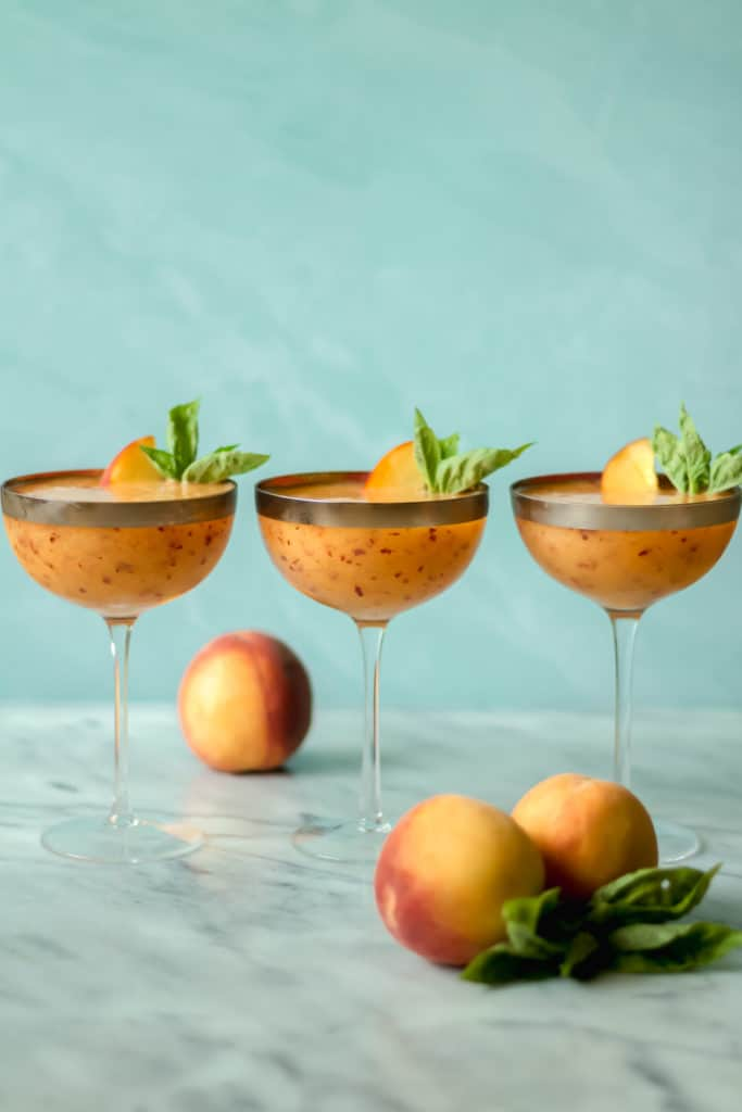 three cocktail glasses filled with peach frose with two peaches in front and one peach behind