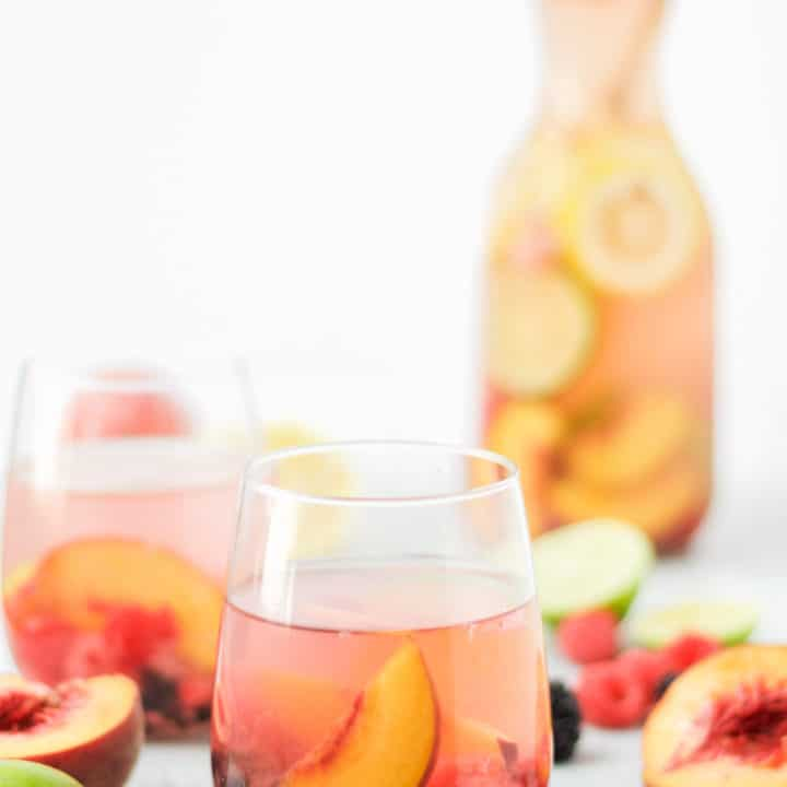 two glasses and a carafe of sparkling peach sangria with fresh fruit