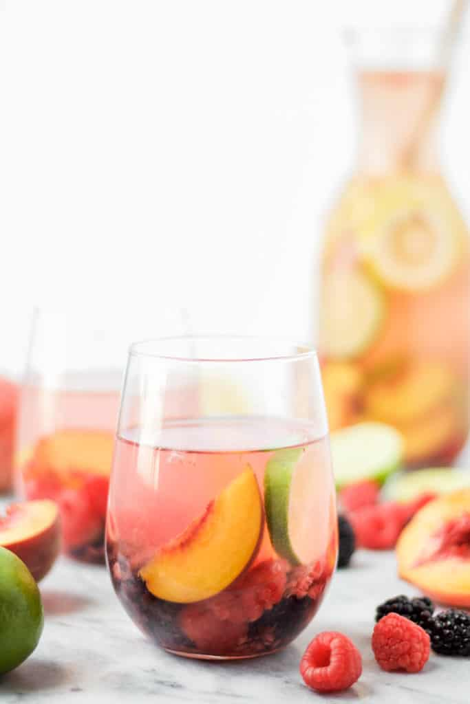 two glasses of sparkling peach sangria with slices of peaches, raspberries and blackberries