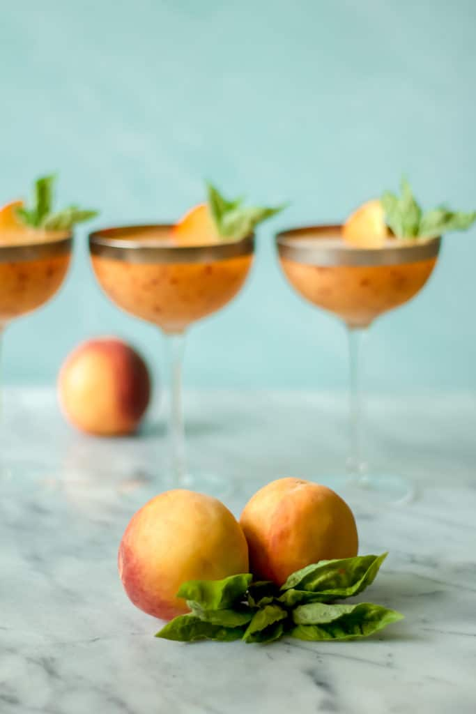 two peaches and a bunch of basil leaves with cocktails in the background