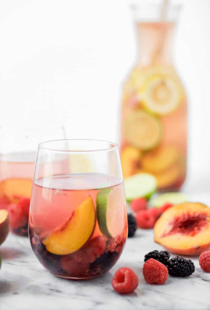 white wine sangria in a wine glass on a marble board with a peach half and raspberries