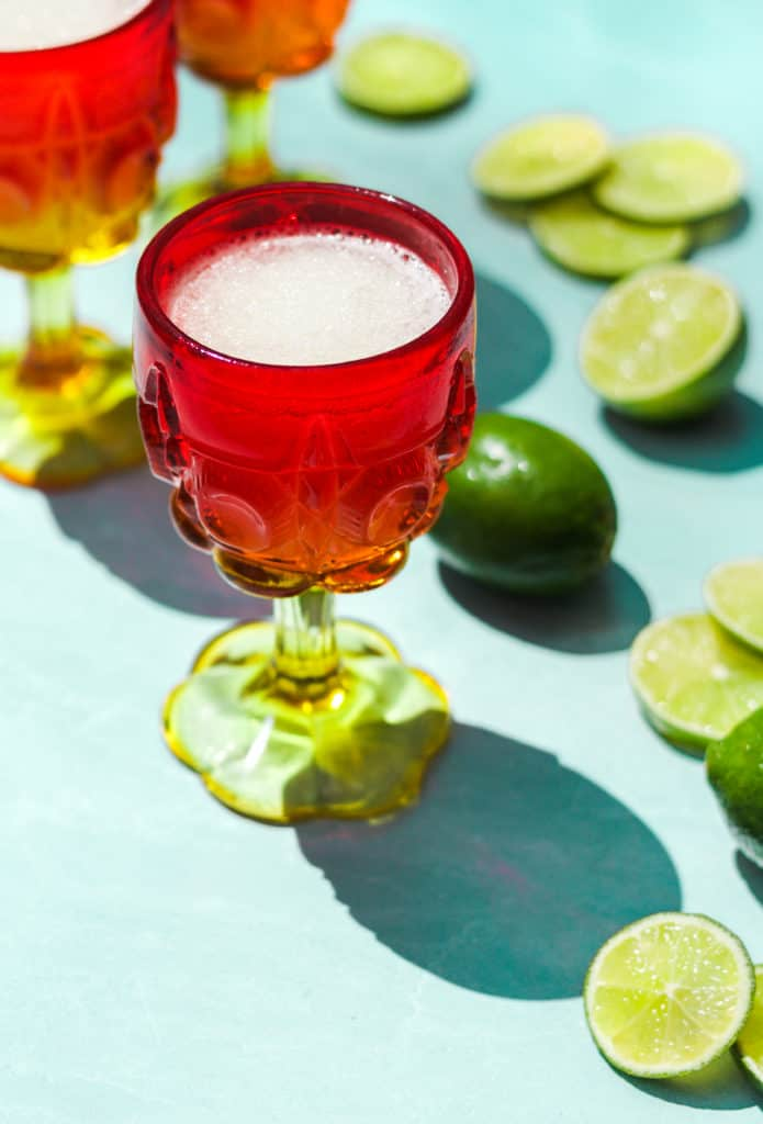 frozen gin and tonic in a red and white glass with a full lime and lime slices on a blue background