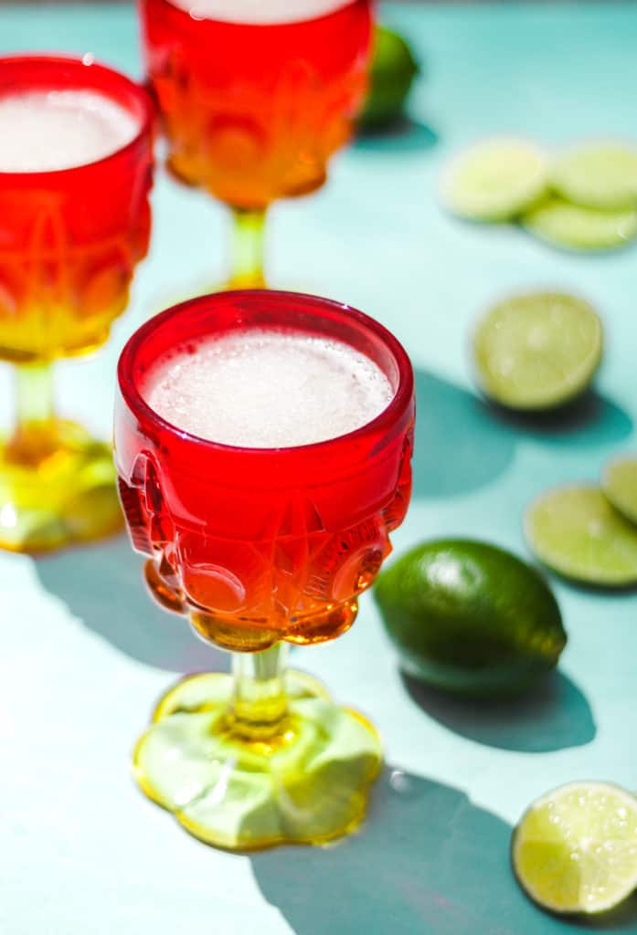 red and yellow cocktail glasses filled with frozen gin and tonic on a blue background with whole and sliced limes