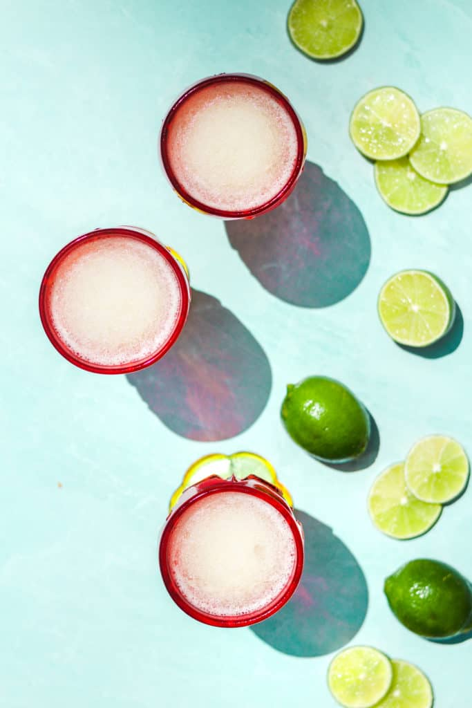 three frozen gin and tonic cocktails with white liquid in red glasses from overhead on a teal background with lime slices