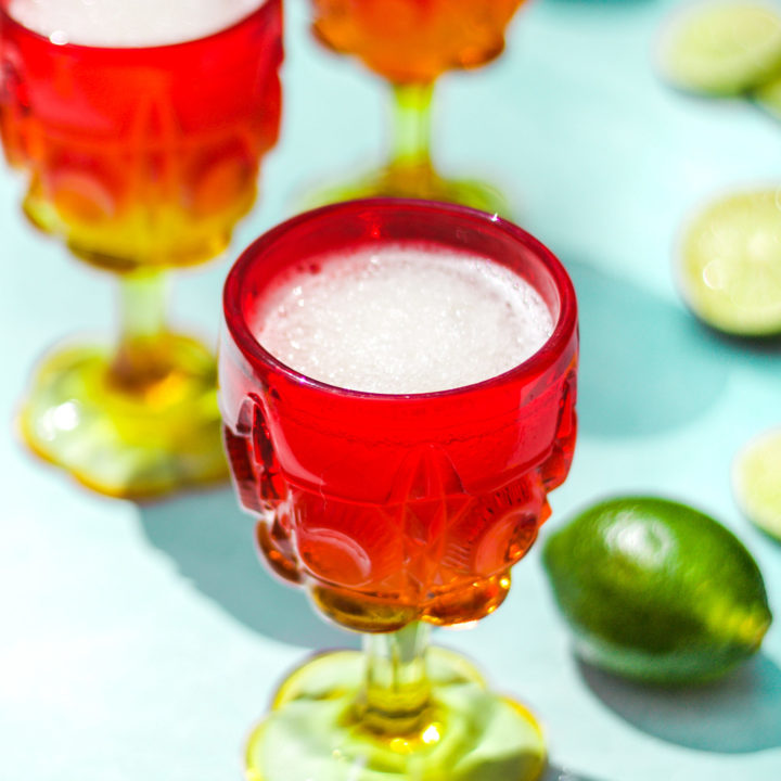 three red and yellow glasses of gin and tonic cocktails next to whole and sliced limes