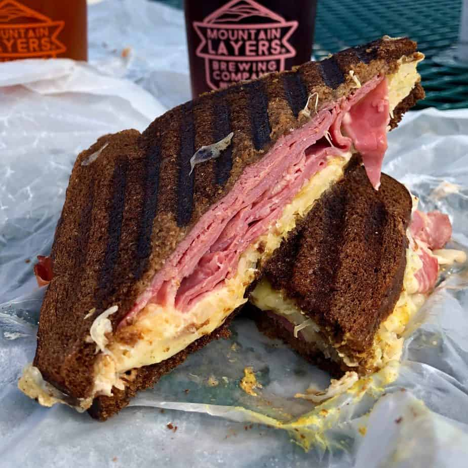 two halves of a ruben sandwich with pumpernickel bread stacked on top of each other with a beer glass and pink logo in the background