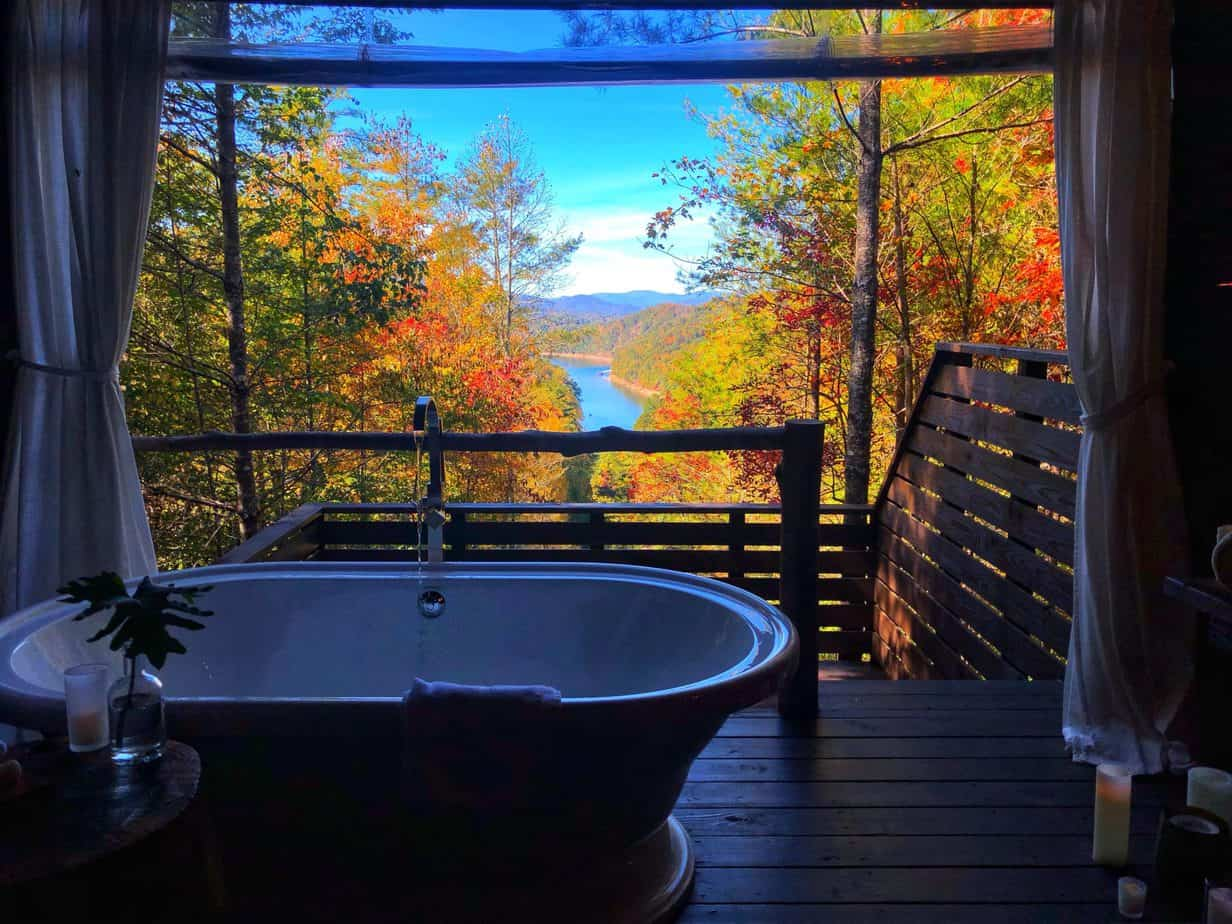 white tub on a wooden porch with colorful fall leaves and a lake in the background
