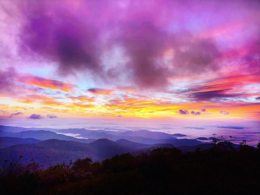 pink, purple, blue and orange sunrise with fog on the mountains at sunrise at black balsam knob hike north carolina
