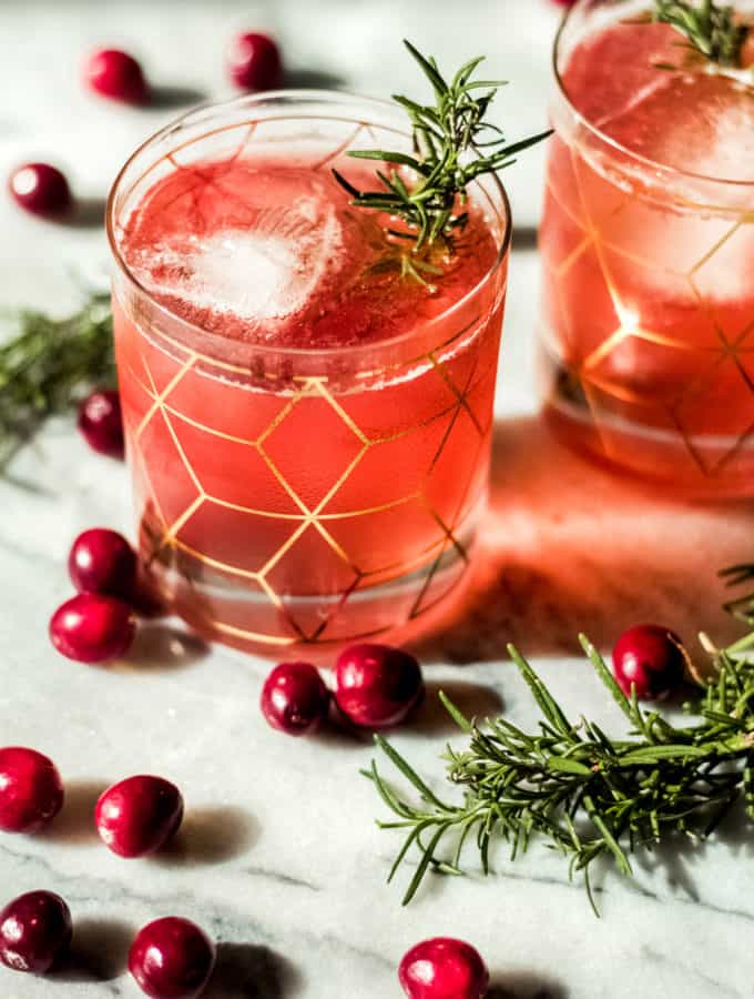 two glasses with gold designeds filled with pink colored cranberry bourbon smash with whole cranberries and rosemary on a marble background