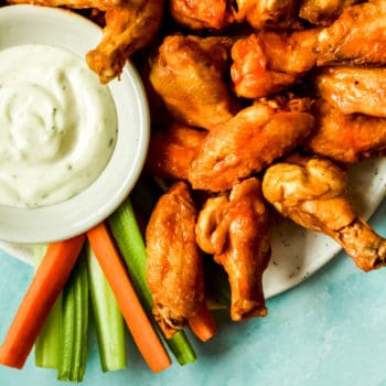 a pile of extra crispy air fryer chicken wings with a side of ranch dressing