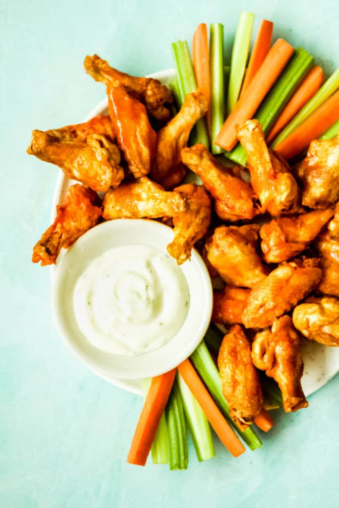 a plate of chicken wings with carrot and celery sticks and ranch sauce