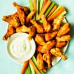 a plate of chicken wings with carrot and celery sticks and ranch sauce with a blue background