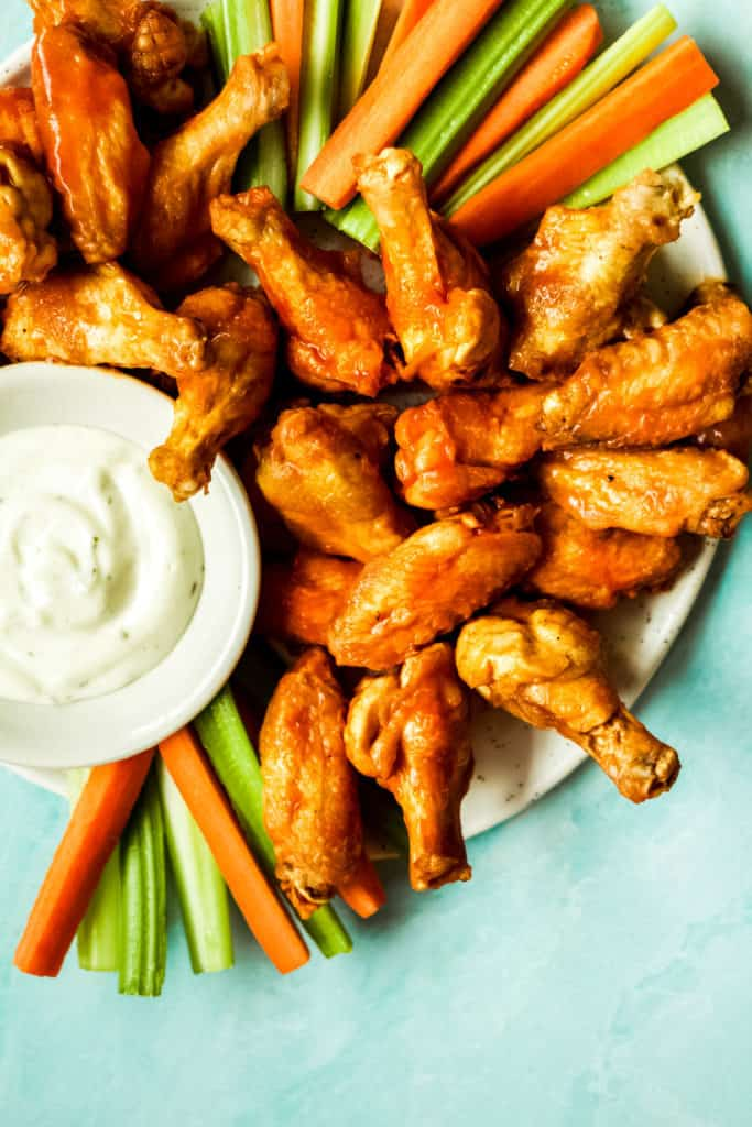 buffalo chicken drumsticks with a bowl of ranch