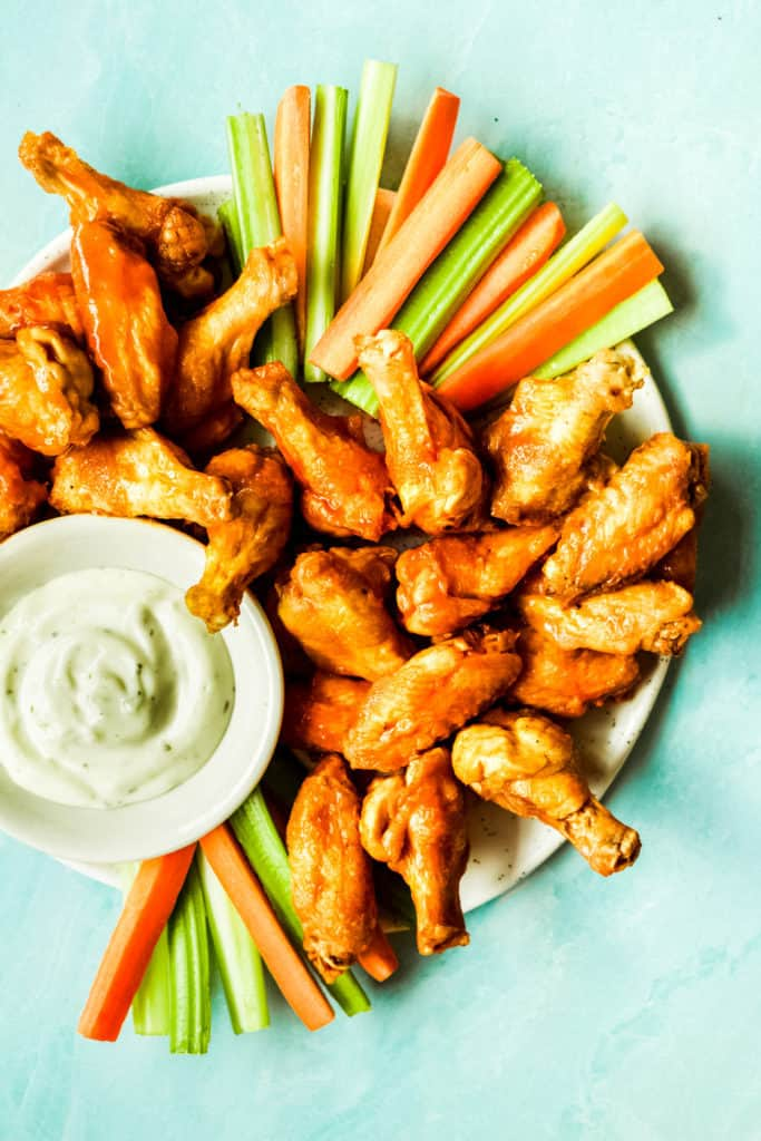 buffalo wings piled high on a plate with carrot and celery sticks and a bowl of ranch