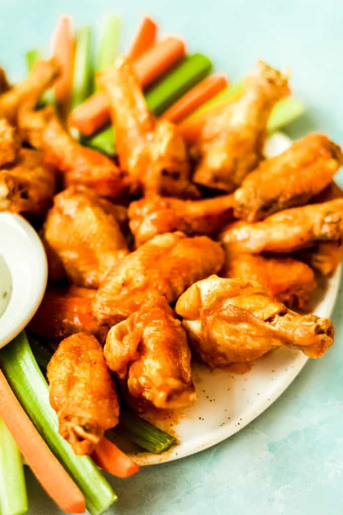 extra crispy air fryer chicken wings piled on a white plate with carrot and celery sticks with a blue background