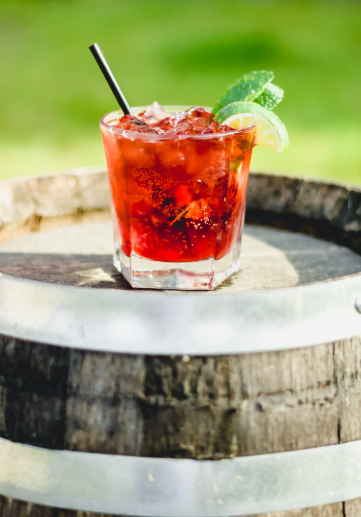 red cocktail with mint and lime wedge garnish on a whiskey barrel with a green backgroun