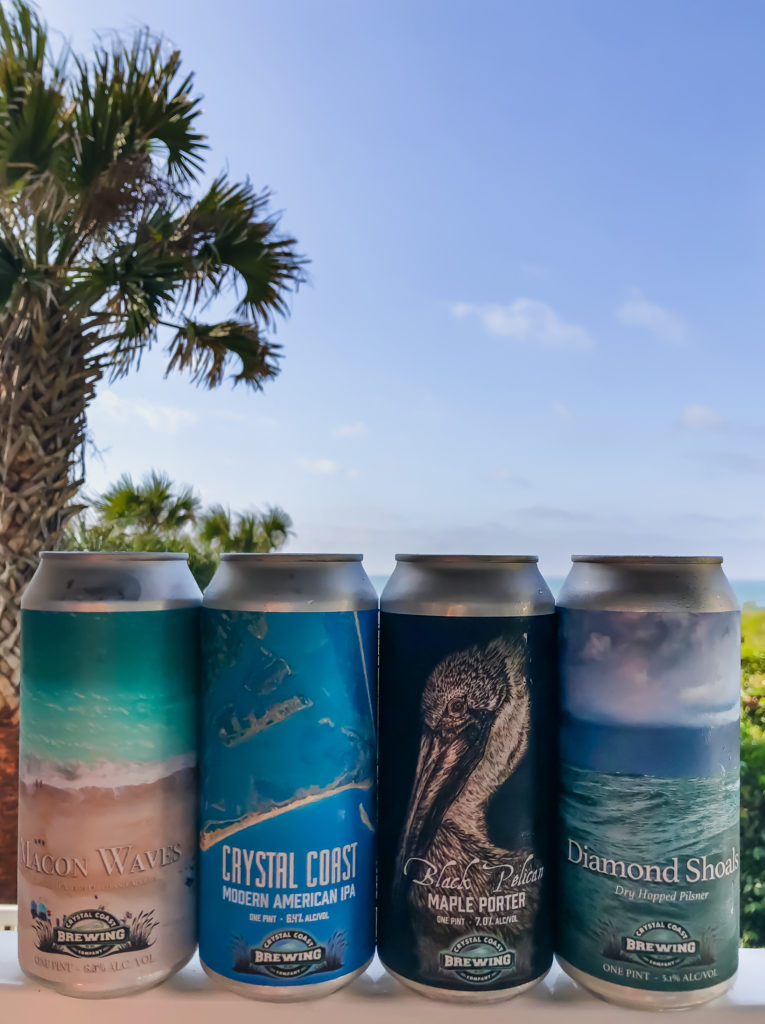 four cans from Crystal Coast Brewing with a palm tree in the background