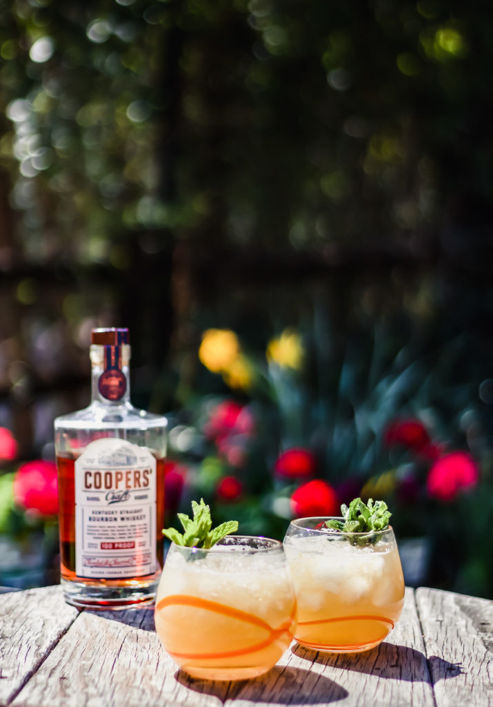 two bourbon peach smash cocktails on a table next to a bottle of coopers craft bourbon with flowers in the background