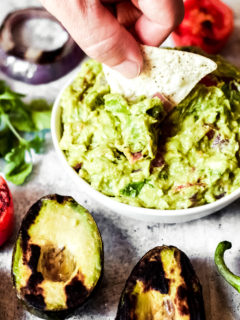 dipping a chip into a whie bowl of vegan guacamole