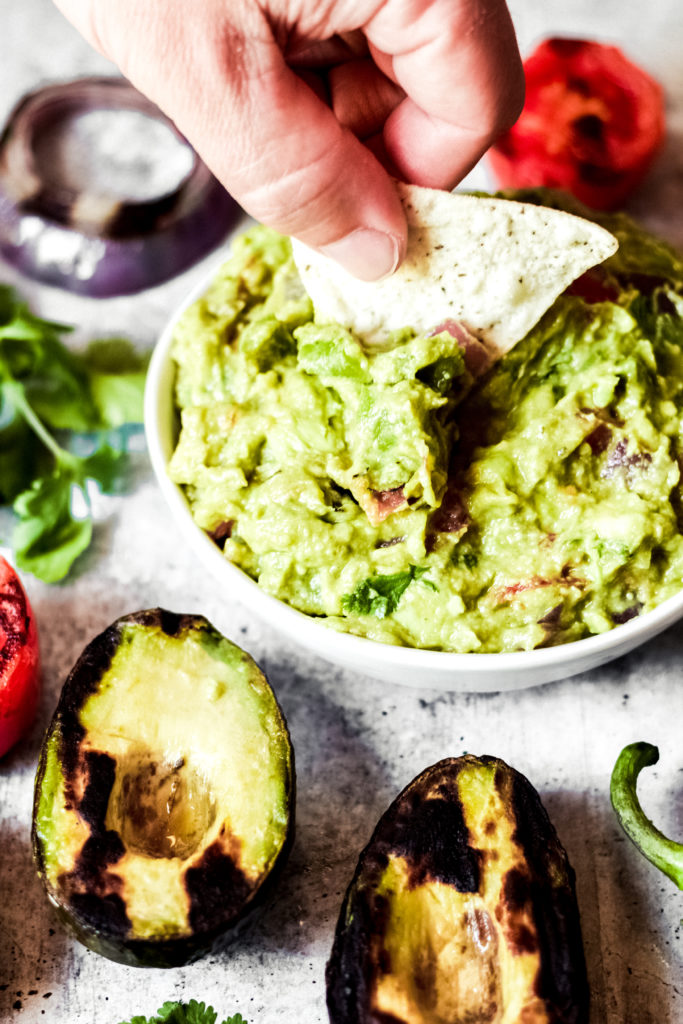 dipping a chip into a white bowl of vegan guacamole