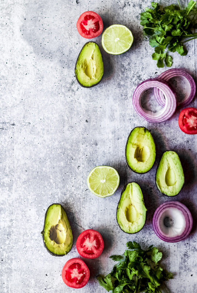 fresh sliced avocado halves, tomatoes, red onions and cilantro on a gray background