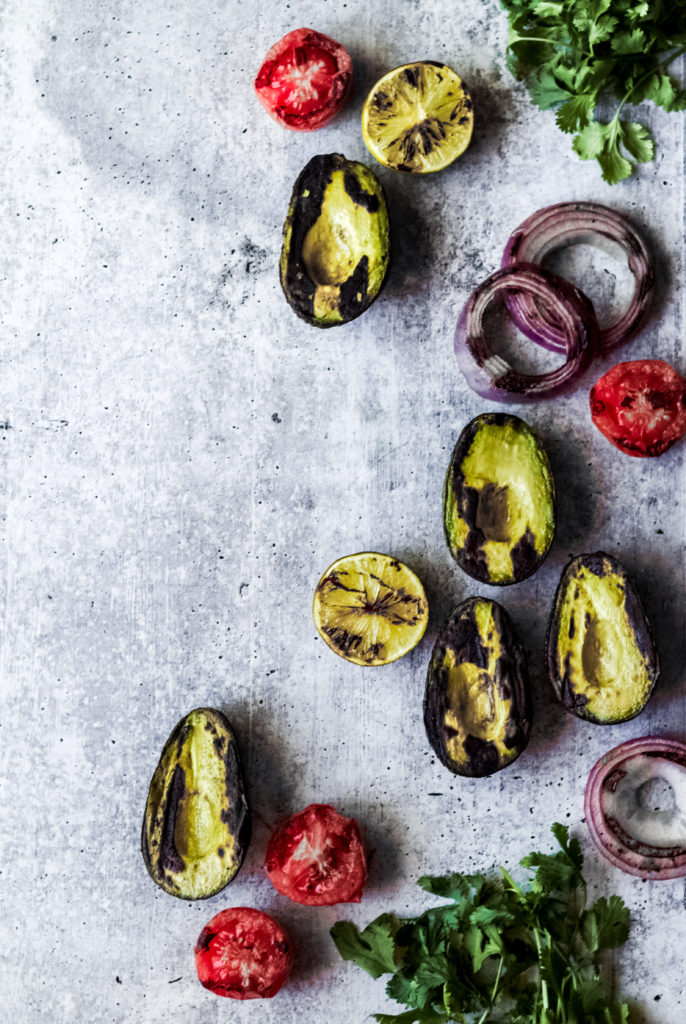 grilled sliced avocado halves, tomatoes, red onions and cilantro on a gray background