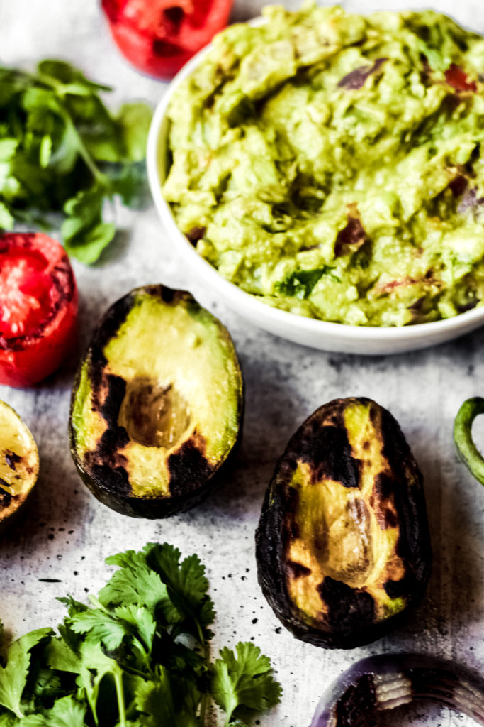 grilled vegan guacamole in a while bowl surrounded by grilled ingredients