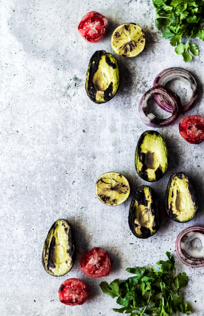 grilled veggies to make vegan guacamole including avocado halves, tomatoes, red onions and cilantro on a gray background